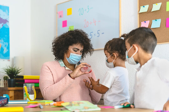 Teacher cleaning hands to student children with sanitizer gel while wearing face mask in preschool classroom during corona virus pandemic - Healthcare and education concept