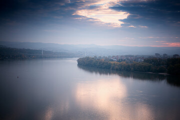 Beautiful autumn landscape, Danube river on a foggy cloudy day, clouds and sky are reflected in water