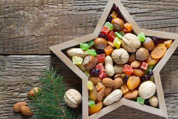 Christmas nuts and dried fruit mix in star-shaped bowl on wooden background assortment of delicacies