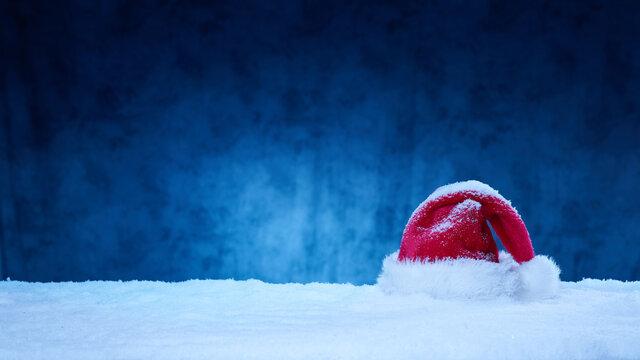Nikolausmütze vor dunklem Hintergrund im Schnee