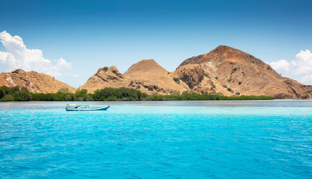 Tranquil picture of small boat in a crystal clear blue ocean with brown mountains in the background in Komodo National Park, Indonesia