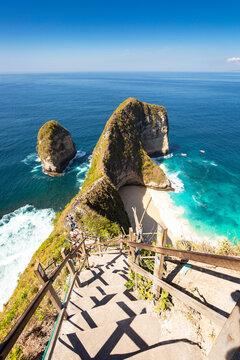 Dinosaurus rock in ocean with very steep stairs going down at Kelingking beach, Nusa Penida, Bali, Indonesia