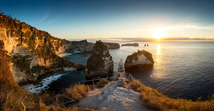 Panorama sunrise over steep cliffs and crystal clear ocean with small temple in foreground at Thousand Islands viewpoint, Nusa Penida, Bali, Indonesia