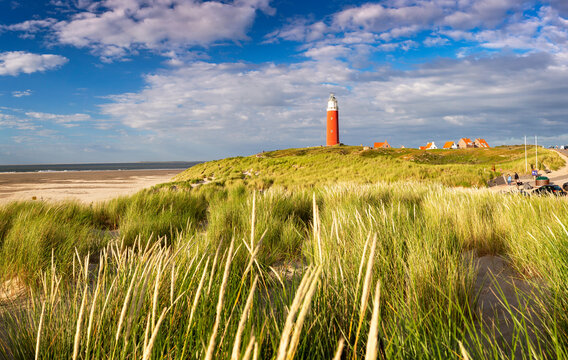 Bright sunlight during sunset over iconic red lighthouse at the island of Texel, The Netherlands