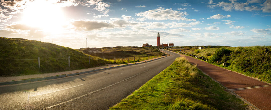 Road to iconic lighthouse surrounded by houses during sunset at the island of Texel, The Netherlands
