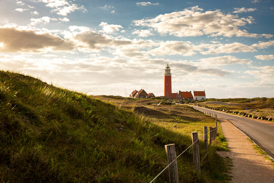 Iconic lighthouse surrounded by houses during sunset at the island of Texel, The Netherlands