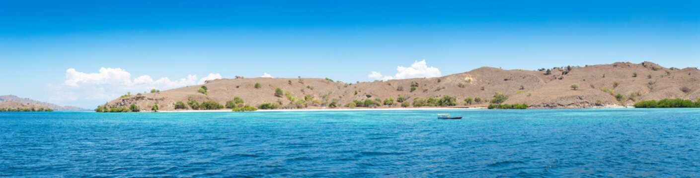 Wide panorama of beatiful clear blue sea with small island in background in Komodo National Park, Indonesia (high resolution)