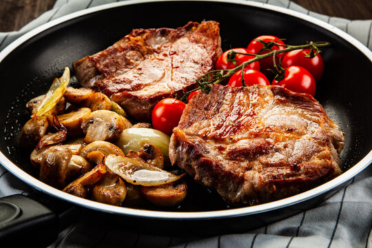 Pork steaks in frying pan with champignons, onion and tomatoes