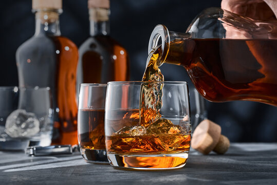 Two glasses of whiskey with ice on a concrete table, a glass of whiskey is poured from a bottle.