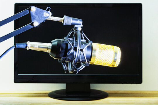 Condenser microphone on the background of a computer monitor