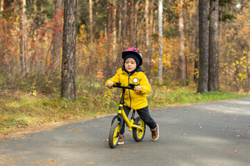 Fototapeta Cute little boy in yellow jacket and protective helmet riding on balance bicycle