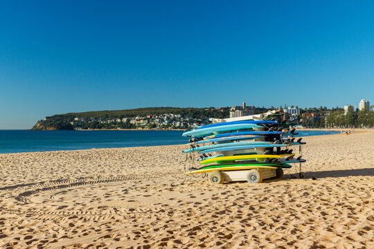 Colorful surfboards stacked on a trailer on the sandy Manly beach with Pacific ocean on the background. Sydney, Australia.