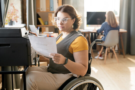 Young disable office worker looking at paper while sitting by xerox machine