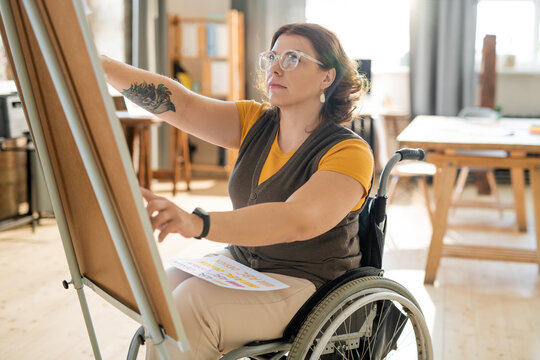 Young female coach in casualwear sitting in wheelchair in front of whiteboard