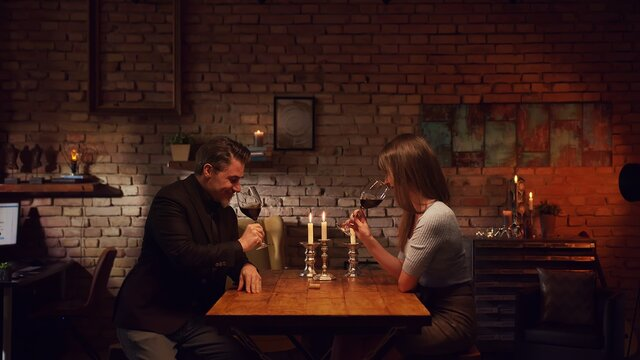 Elegant couple having romantic dinner at home, sitting at table in living room drinking red wine. Stay at home concept.