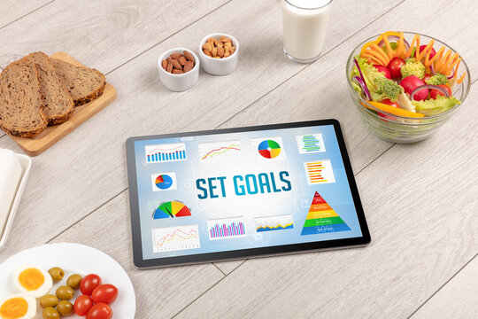 Organic food and tablet pc showing SET GOALS inscription, healthy nutrition composition
