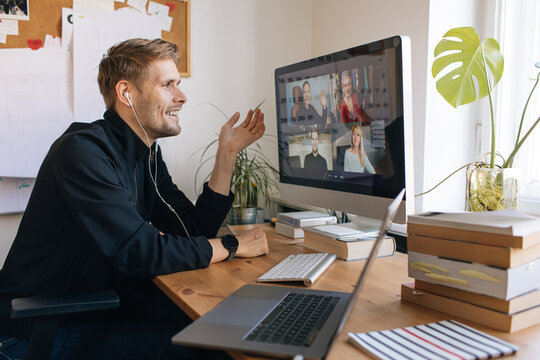 Young man having Zoom video call via a computer in the home office. Stay at home and work from home concept during Coronavirus pandemic. Smiling handsome man teleworking