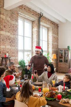 Mature man in Santa cap standing by wife during family dinner by festive table
