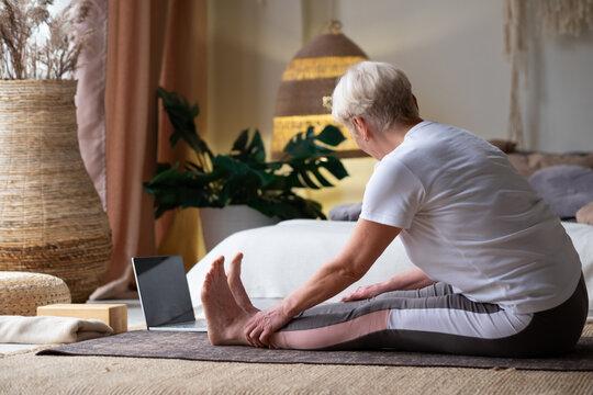 Sporty senior woman practicing yoga, doing seated forward bend pose, paschimothanasana