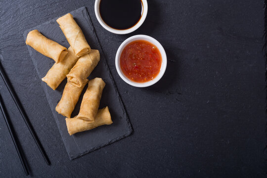 Fried spring rolls with vegetables on rustic background