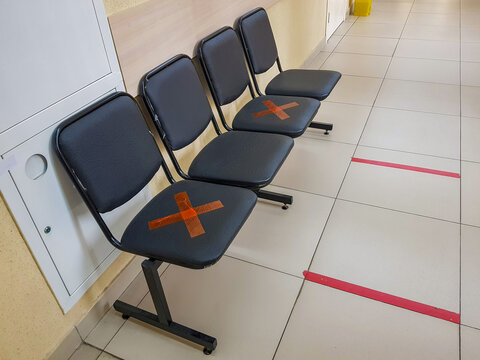 Four leather chairs in the hospital corridor. Red tape markers for social distancing in a pandemic