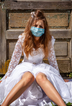 sad young bride in white dress during pandemic