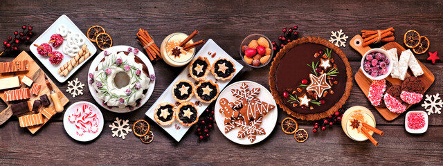 Assorted Christmas holiday desserts and sweets. Top view panoramic table scene over a rustic wood background. Bundt cake, chocolate pie, mincemeat tarts, cookies, fudge and eggnog.