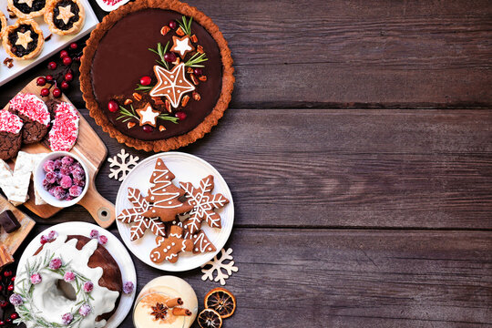 Mixed Christmas holiday desserts and sweets. Top down view side border over a dark wood background. Bundt cake, chocolate pie, mincemeat tarts, cookies and eggnog.