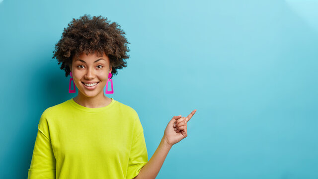 Horizontal shot of cheerful Afro American woman in casual t shirt points away on copy space suggests follow this direction or click on link poses against blue background. Your advertising here