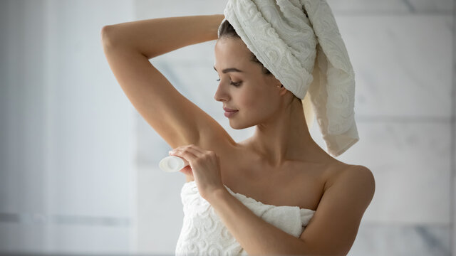 Little but important detail. Pretty millennial female wrapped in towel putting solid deodorant antiperspirant to armpit just after shower or bath enjoying favorite flavor scent preparing to leave home