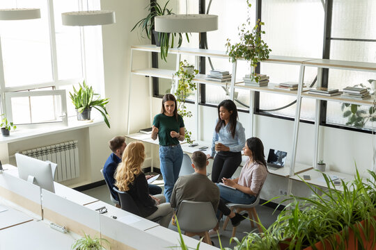 Workshop at break time. Group of six focused concentrated diverse business people corporate staff employees executives listening to millennial woman team leader creating idea plan talking interacting