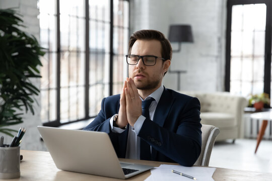 Hopeful young businessman sitting at workplace table with folded hands, praying God for good luck before online negotiations meeting or starting new project development on computer, feeling faithful.