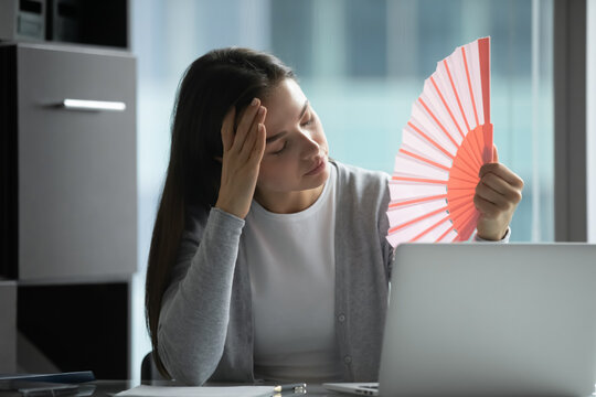 Impossible to work without air conditioner. Unhappy sad young female corporate employee feeling unhealthy overtired of extreme abnormal heat in office losing motivation enthusiasm for doing job good