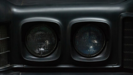 Headlights of a black old retro car. Close-up. Details.