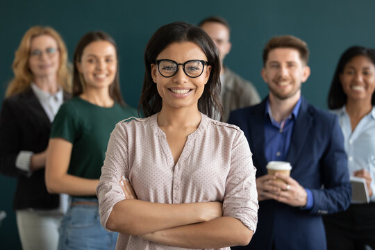 Multiethnic crew. Young biracial female confident qualified specialist hr ceo leader head member of diverse corporate team posing for portrait holding arms crossed on chest smiling looking at camera