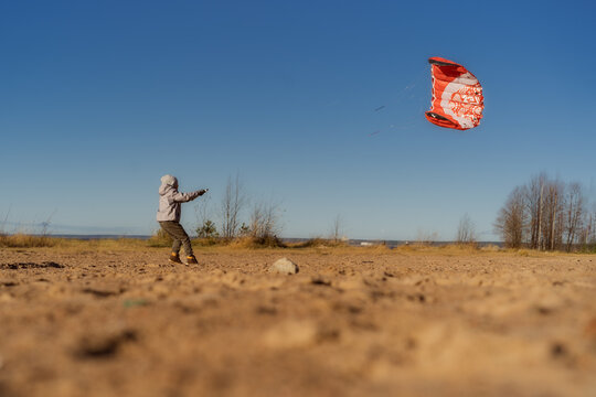 a happy caucasian boy flying a kite on the beach, Image with selective focus