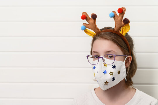 Close up portrait of teenage girl wearing decorated white medical fabric mask, isolated over white background. Stay home. Christmas coronavirus concept. Copy space