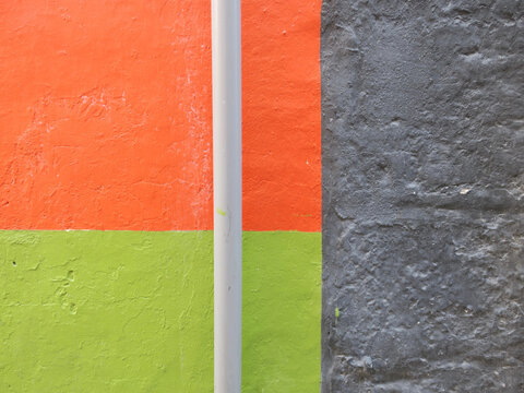 stone wall painted in three colors, orange, green and gray and a drainpipe