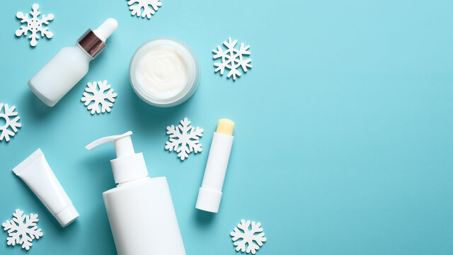 Set of cosmetic products on blue background, flat lay. Winter skin care concept.