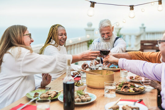 Multiracial senior people enjoy dinner at home on patio and cheering with wine