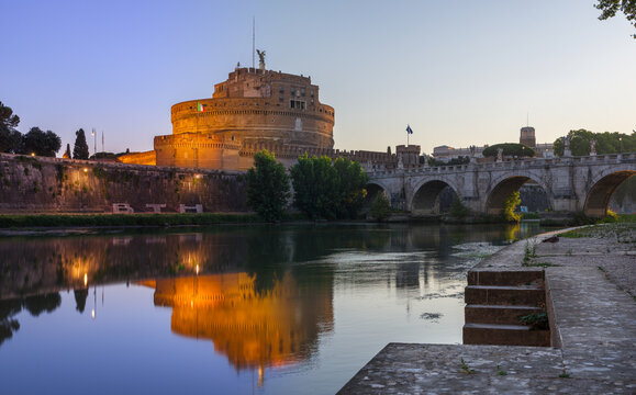Sunrise long exposure of Castel Sant'Angelo ancient tumb and fortress illuminated at night, reflecting on the Tiber river, with the Bridge of the Holy Angel and riverbank staircase in Rome, Italy