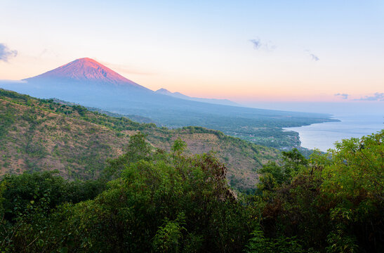 Landscape of Bali north coastline at sunrise, with Mount Agung volcano peak and forest slopes, and Java sea, from hilltop near Amed, Bali, Indonesia