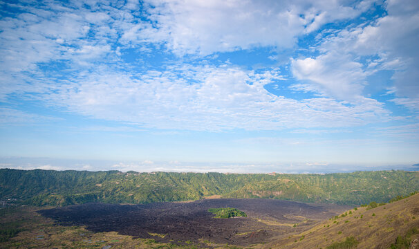 Panorama of popular trek destination Mount Batur eastern ridge at sunrise, with black solidified lava flow field, near Batur, Bali, Indonesia
