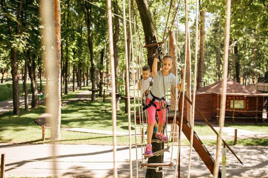 Little female climber leisures in rope park
