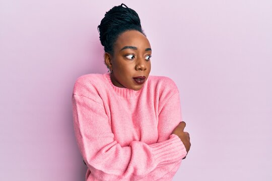 Young african american woman wearing casual winter sweater shaking and freezing for winter cold with sad and shock expression on face