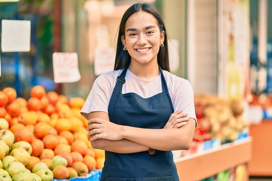 Young latin shopkeeper girl with arms crossed smiling happy at the fruit store.