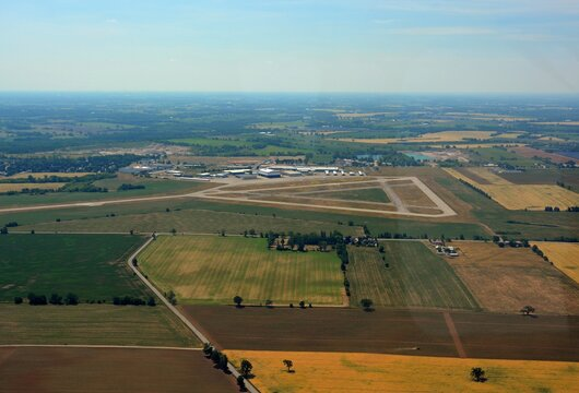 Aerial view of the Brantford Municipal airport in southern Ontario, view of the runways and hangars and surrounding farmland