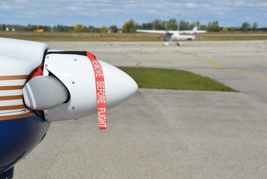 Closeup of a propeller with the Remove before flight banner still attached, airport and another propeller airplane blurred in the background