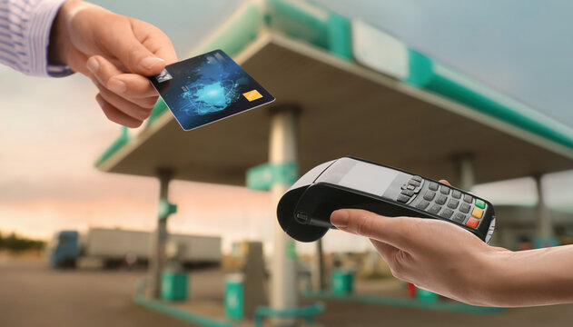 Woman paying for fuel using credit card via payment terminal at gas station, closeup