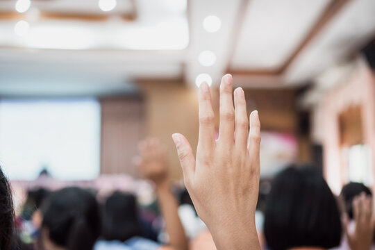 Audience or students raising hands up at conference to answer question while speaker speech at seminar hall with crowd groups, arms of large group in classroom for vote or questions